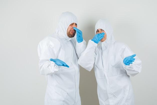 Twee artsen die hun neus dichtknijpen vanwege een slechte geur in beschermende pakken