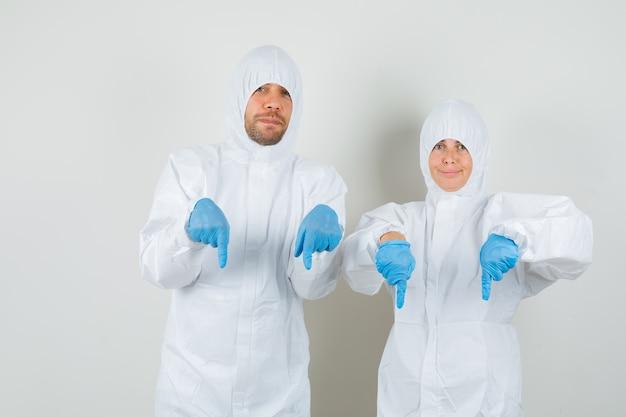 Twee artsen die hun vingers naar beneden richten in beschermende pakken