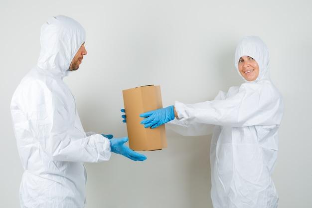 Twee artsen die kartonnen doos aan elkaar in beschermend kostuum geven