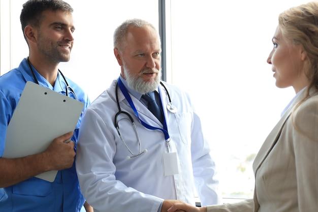 Twee artsen en vrouwelijke patiënt handen schudden voor overleg in het kantoor van een modern medisch centrum.