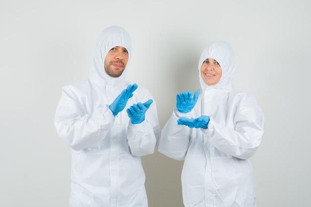 Twee artsen in beschermende pakken, handschoenen applaudisseren en op zoek gelukkig