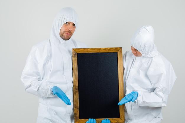 Twee artsen in beschermende pakken, handschoenen die bord tonen en zelfverzekerd kijken