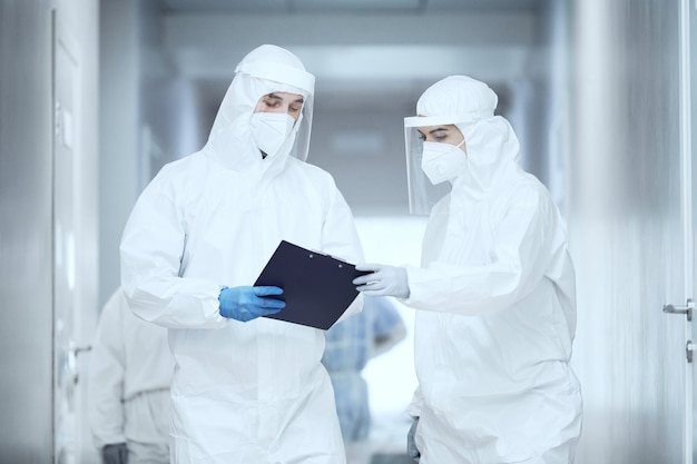 Twee artsen in beschermende uniformen die in de ziekenhuisgang staan en samen medische kaart onderzoeken