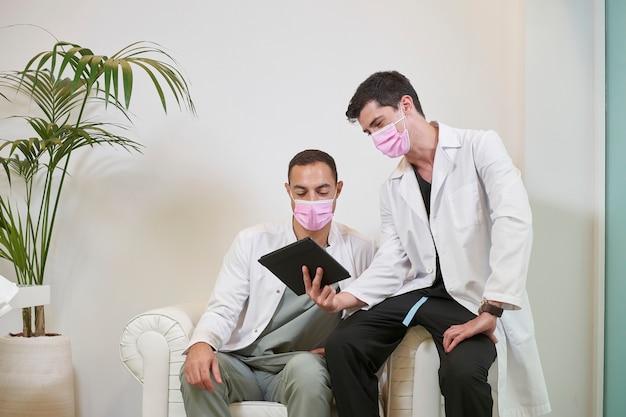 Twee artsen in de wachtkamer met maskers kijken naar het tabletscherm in een gynaecologische, tandheelkundige of cosmetische kliniek. medisch concept.