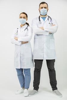 Twee artsen in witte jas en beschermend masker staan met armen gevouwen