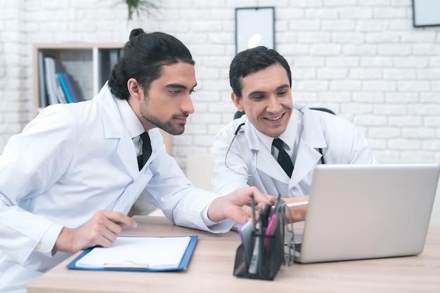 Twee artsen kijken naar iets op de laptop.