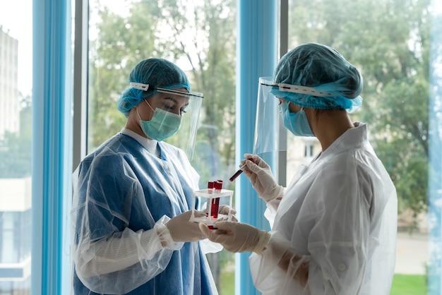 Twee artsen kijken op reageerbuis met bloed met een positieve reactie op coronavirus. gezondheidszorg