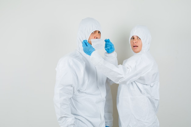 Twee artsen medische masker op elkaars gezicht zetten in beschermende pakken