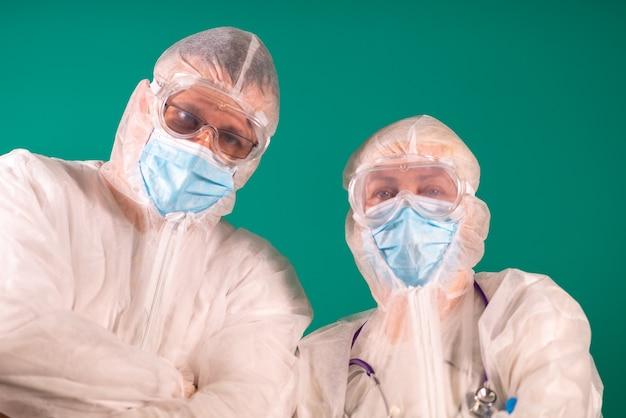 Twee artsen met gelaatsschermen in pbm-pak uniformen die medische beschermende maskers dragen