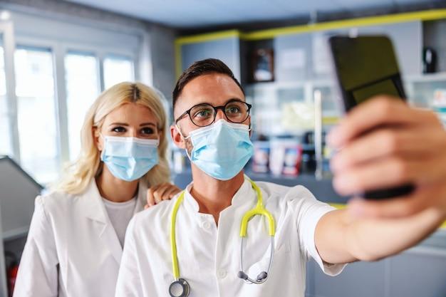 Twee artsen met gezichtsmaskers staan in het ziekenhuis en nemen selfie. a