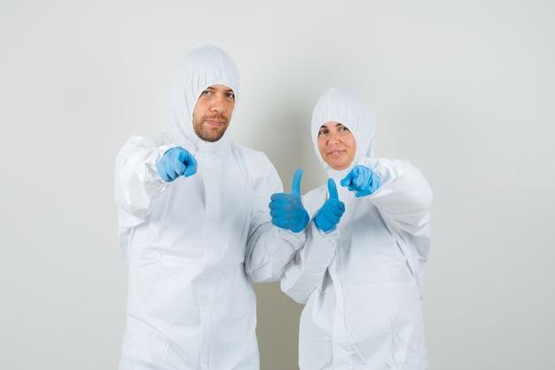 Twee artsen wijzend op camera en duim opdagen in beschermende pakken