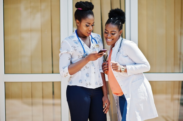 Twee artsenwijfje bij laboratoriumlaag met stethoscoop stelde openlucht tegen kliniek bekijkend mobiele telefoon