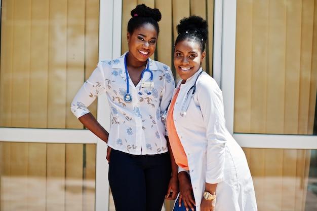Twee artsenwijfje bij laboratoriumlaag met stethoscoop stelde openlucht tegen kliniek