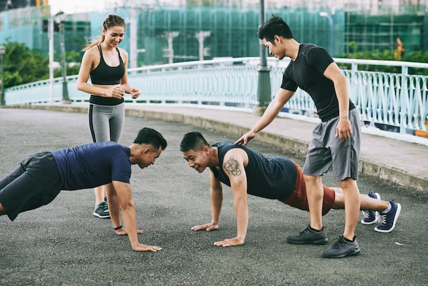 Twee atleten concurreren doen pushups buitenshuis, hun vrienden tellen en ondersteunen