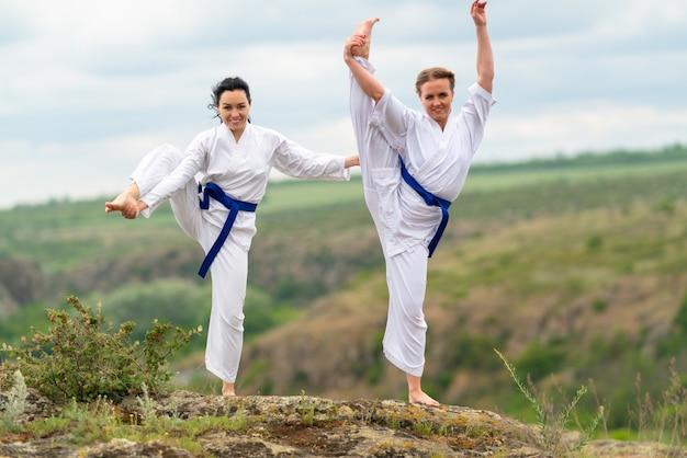 Twee atletische aantrekkelijke geschikte jonge vrouwen in vechtsporttunieken die in openlucht uitoefenen