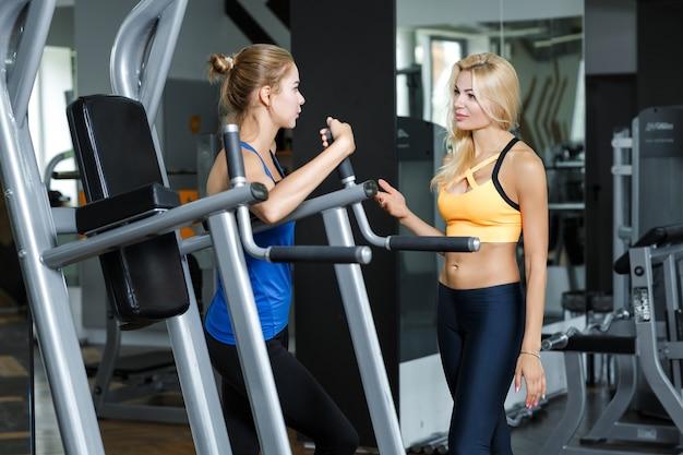Twee atletische blonde vrouwen praten in sportschool meisje communiceert met trainer