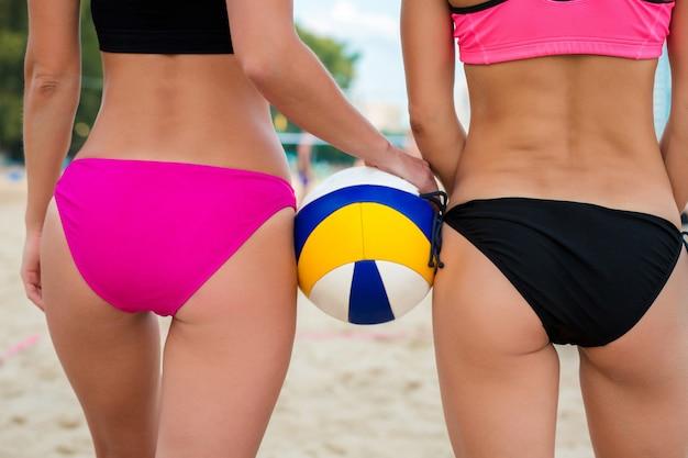 Twee atletische meisjes volleyballers houden volleybal bal en poseren op het strand, close-up shot