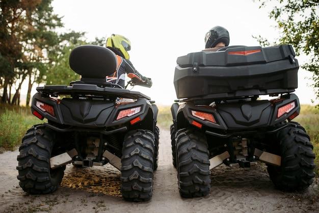 Twee atv-rijders in helmen, achteraanzicht, quad