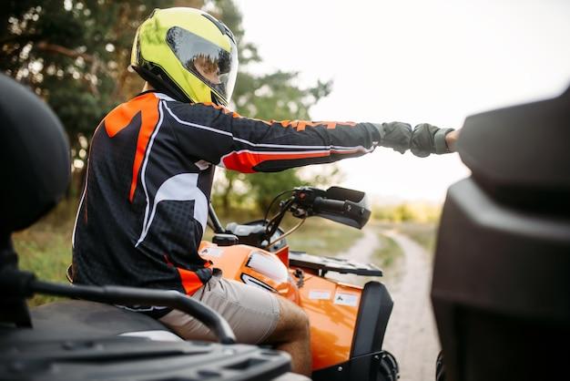 Twee atv-rijders slaan vuisten voor geluk, achteraanzicht