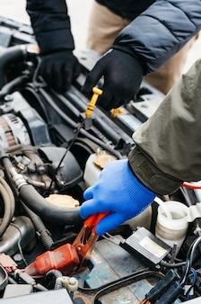 Twee automonteur-ingenieurs controleren, repareren van de auto, maken onderhoud uitgebreide automatische controles.