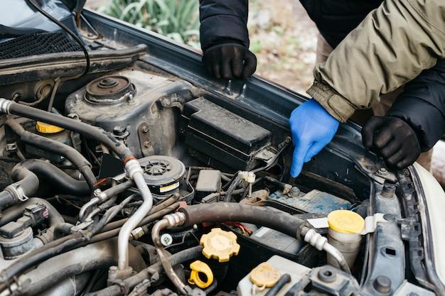 Twee automonteur-ingenieurs controleren, repareren van de auto, maken onderhoud uitgebreide automatische controles