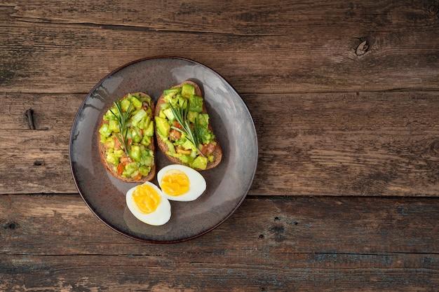 Twee avocado sandwiches en gesneden gekookte eieren op een houten achtergrond.
