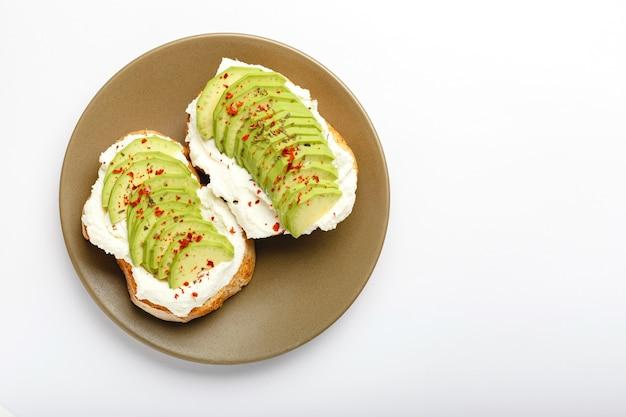 Twee avocadotoosts, sandwich met avocado. verse avocado gesneden op toast van tarwebrood, roomkaas.