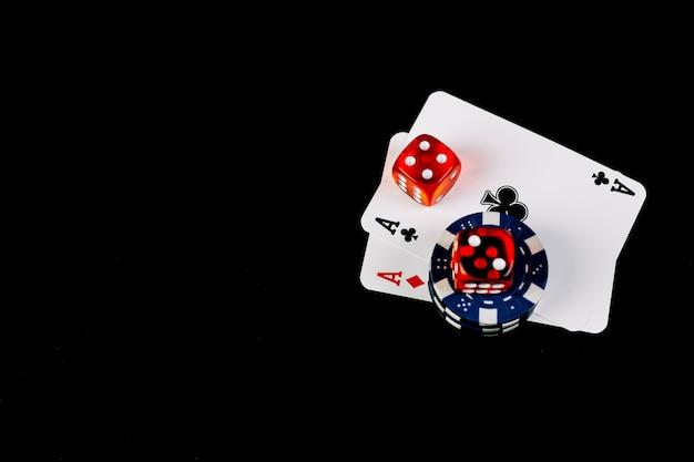 Twee azen speelkaarten met dobbelstenen en pokerfiches op zwarte achtergrond