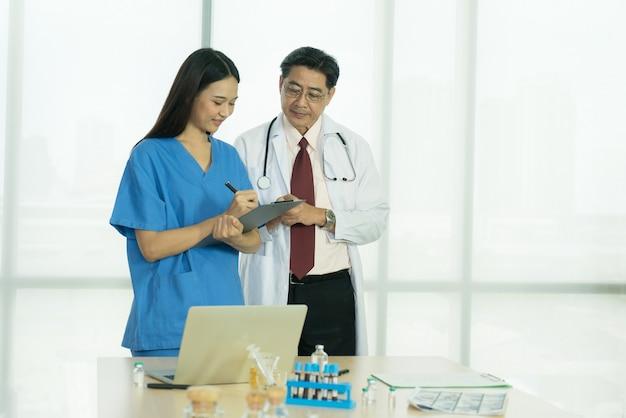 Twee aziatische artsen die samen staan en praten bespreken in de vergaderruimte meeting
