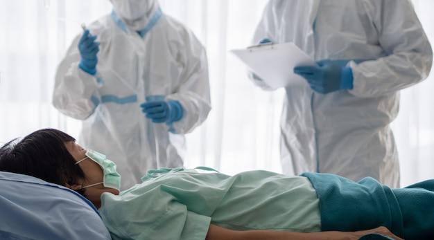 Twee aziatische artsen dragen een pbm-pak met een n95-masker en een gelaatsscherm, behandelen en gebruiken een zuurstofmasker met een coronavirus-geïnfecteerde patiënt in een kamer met negatieve druk.