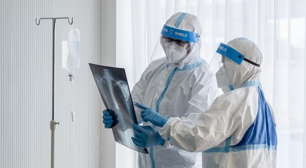Twee aziatische artsen dragen een pbm-pak met een n95-masker en een gelaatsscherm, onderzoeken de röntgenfilm van de longborst van een coronavirus-geïnfecteerde patiënt in een kamer met negatieve druk.