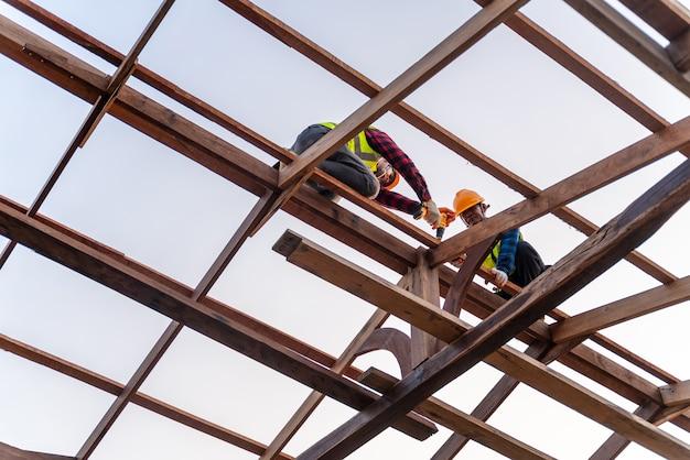Twee aziatische bouwvakkers installeren nieuw dak, dakgereedschap, elektrische boor gebruikt op nieuwe daken van houten dakstructuur, teamwork bouwconcept.