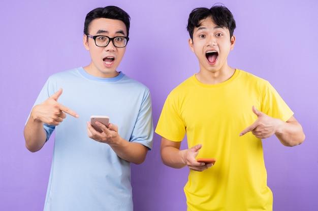 Twee aziatische broers met behulp van mobiele telefoons op paarse achtergrond