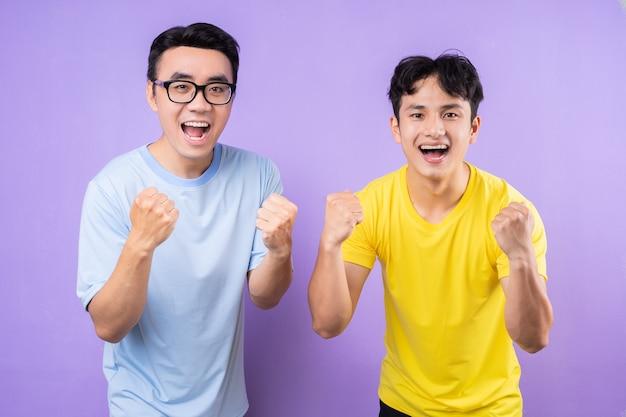 Twee aziatische broers poseren op paarse achtergrond