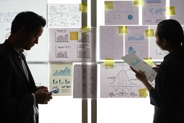Twee aziatische collega's die zich door venster met grafieken en diagrammen bevinden