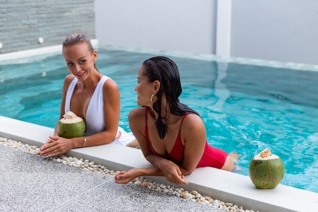 Twee aziatische en kaukasische vrouwenvrienden met make-up in zwembad bij villa