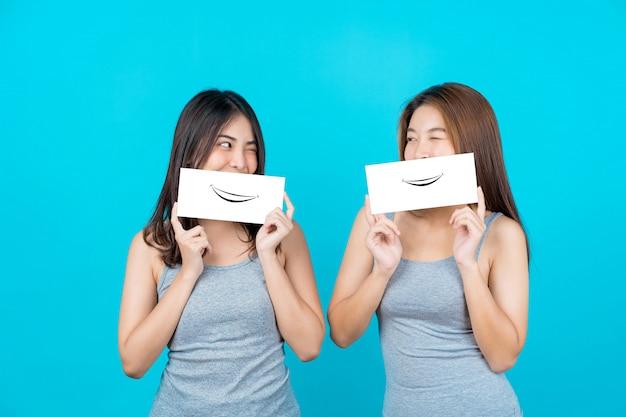 Twee aziatische glimlachende jonge vrouwen die en met affiches op geïsoleerde blauwe kleurenmuur tonen voorstellen