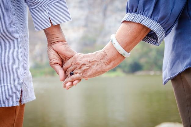 Twee aziatische hogere vrouwen houden elkaars hand vast
