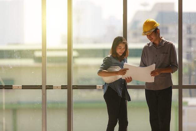 Twee aziatische ingenieur, man met gele veiligheidshelm en vrouw met witte staande en pratend in de buurt van hoge vliesgevel glazen frame in bouwplaats. beiden kijken naar blauwdrukpapier.