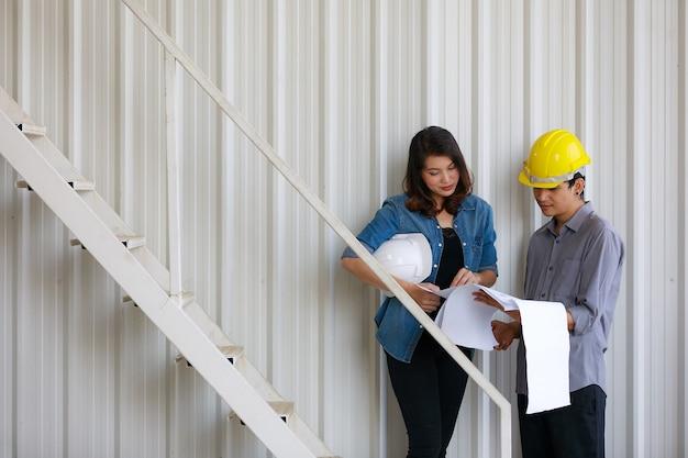 Twee aziatische ingenieurs, man en vrouw, bespreken in bouwwerf