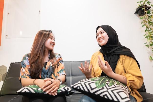 Twee aziatische jonge meisjes chatten zittend in een koffieshop