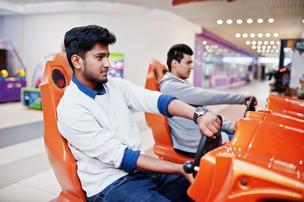 Twee aziatische jongens strijden op de speed rider arcade game race simulator machine