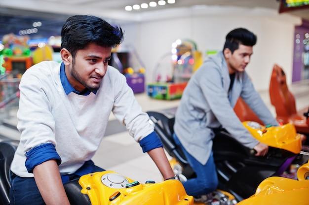 Twee aziatische jongens strijden op speed rider arcade game motorsport simulator machine