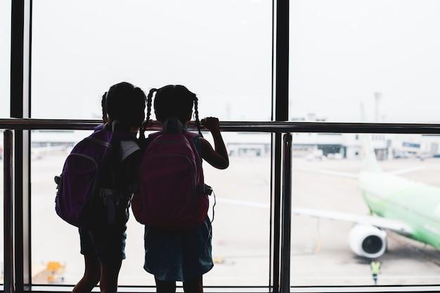 Twee aziatische kind meisjes met rugzak vliegtuig kijken en wachten op instappen in de luchthaven