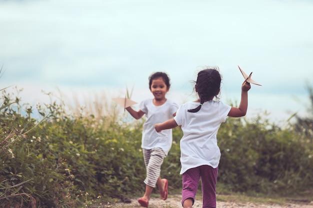 Twee aziatische kinderen die met stuk speelgoed document vliegtuig in de weide samen spelen