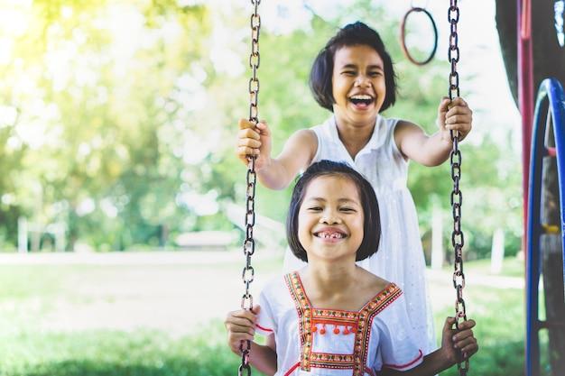 Twee aziatische kinderen meisjes plezier op schommel