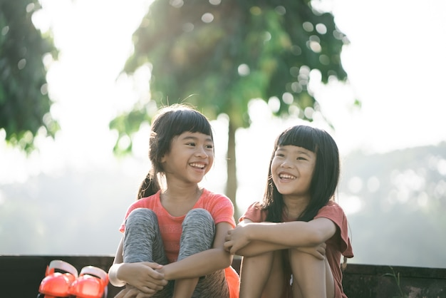 Twee aziatische kinderen nemen 's ochtends een pauze in het park