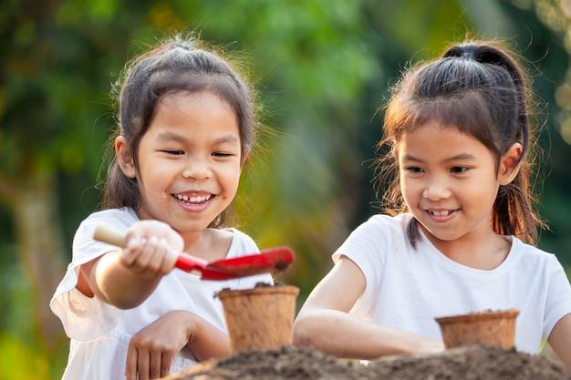 Twee aziatische kindmeisjes bereiden grond voor op het samen planten van jonge zaailingen in kringloopvezelpotten