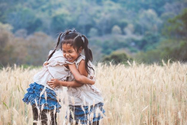 Twee aziatische kindmeisjes die elkaar met liefde koesteren en samen op het gerstgebied spelen
