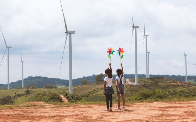 Twee aziatische kindmeisjes die met het stuk speelgoed van de windturbine spelen en samen het gebied van de windturbine bekijken